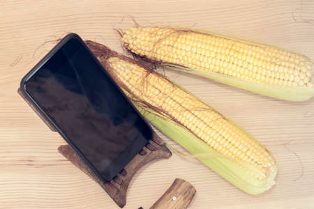 mobile phone on a stand and two yellow corn