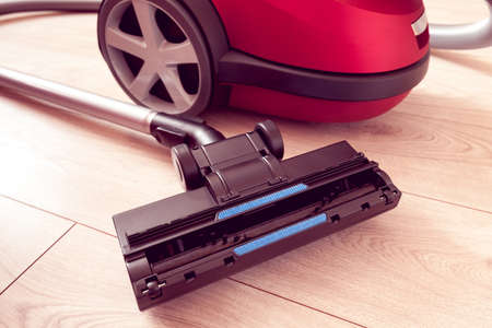 vacuum cleaner of red color on a gray laminate Imagens
