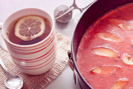 red cheesecake in baking dish with tea Imagens