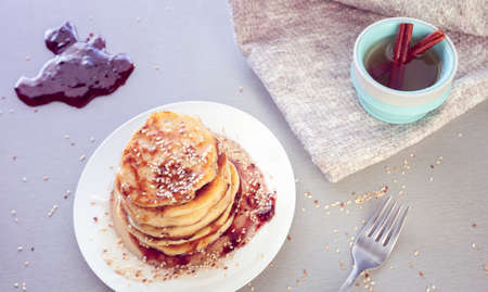 pancakes sprinkled with sesame and tea with cinnamon Imagens