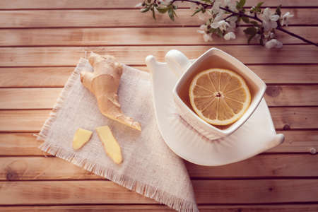 ginger and cup of tea with lemon on a wooden background Imagens
