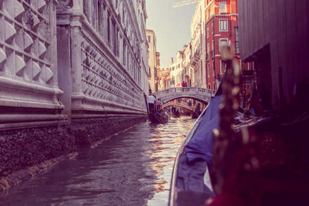 narrow canal in Venice with white marble architecture and bridge, view from gandola