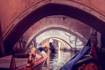 The gondolier floats on a narrow canal in Venice under the bridge Imagens