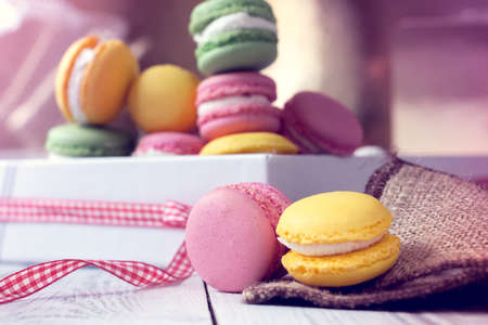 yellow and pink macaroons on a sackcloth and other macaroons in a box on the background 写真素材
