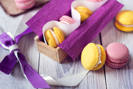 yellow and pink macaroons in a violet box with bow-knot Imagens