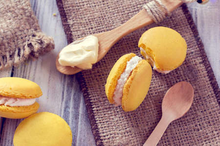 yellow macaroons with cream in a spoon 写真素材