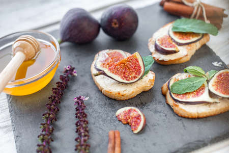 honey and toasteres smeared by ricotta with  sliced figs