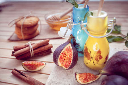the yogurt decorated with a fig in glass jars and cinnamon, cookie and honey Imagens