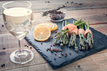 bunches of asparagus wrapped in salmon with spices and wine on a black board Imagens