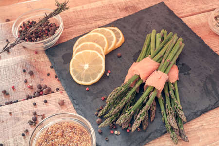 bunches of asparagus wrapped in salmon with spices on a black board