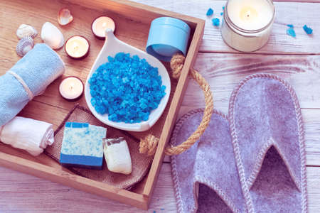 SPA consist from blue sea salt, soap in a wooden tray and slippers Imagens