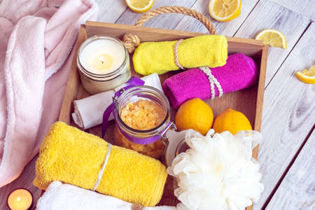 SPA consist from bathrobe, yellow sea salt, lemons and other accessories for bath in a wooden tray Imagens