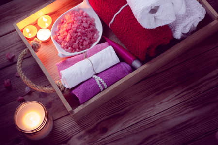 SPA consist from colorful towels, pink sea salt and candles on a wooden tray. Picture in Low-key lighting Imagens