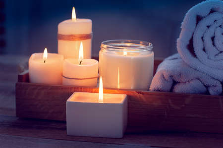 SPA consist from candles and  towels on a wooden tray. Picture in Low-key lighting