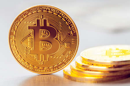 golden bitcoin on the background of a heap of other bitcoins