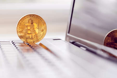 gold bitcoin in a laptop keyboard Imagens