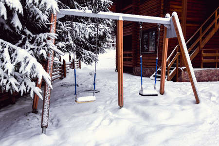 two childrens swings in the yard covered with snow Imagens
