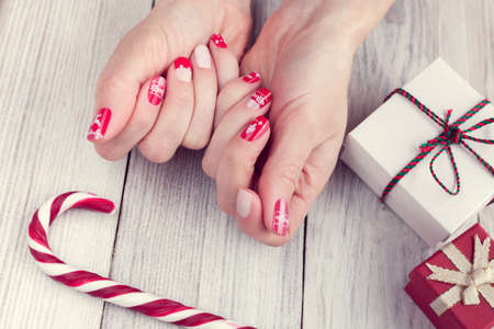 Art christmas manicure on female hands. Picture on a white wooden background with gifts and lollipop