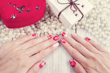 Art christmas manicure on female hands. Picture on a white wooden background with gifts and white beads