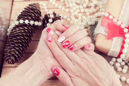 Art christmas manicure on female hands. Picture on a wooden background with cones, gift and white beads