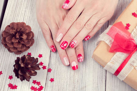 Art christmas manicure on female hands. Picture on a white wooden background with gift and two cones