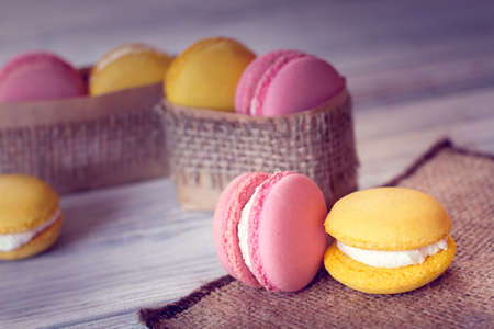 yellow and pink macaroons in boxes packed with burlap