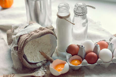 flour with spoon in a sack and broken eggs with milk and water on a background