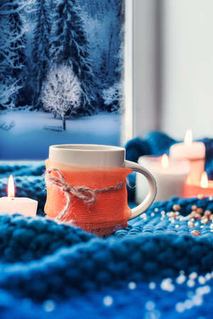 orange cup with coffee and candles on the background of a window through which the winter forest is visible