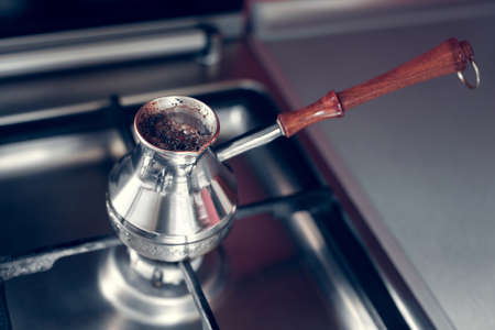 cezve with a wooden handle on a gas stove