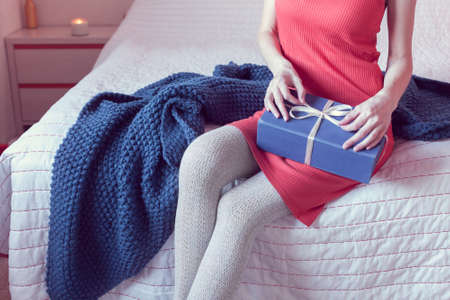 girl in a red dress opens a gift while sitting on the bed 版權商用圖片