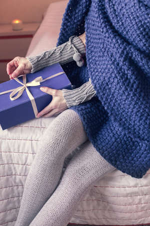 girl wrapped in a plaid, opens a gift while sitting on the bed