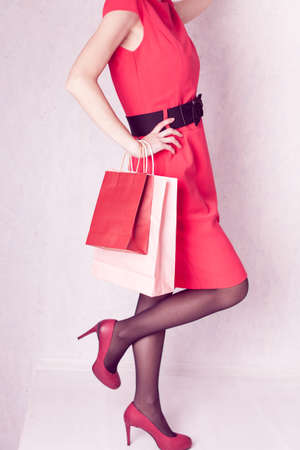 girl in a red dress and high heels holds packages in her hand 版權商用圖片