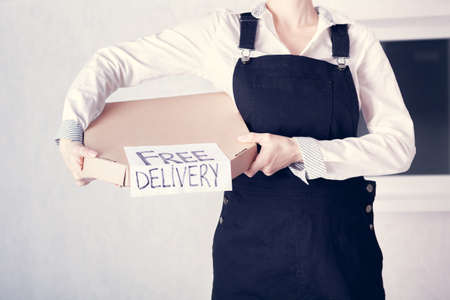 Courier holding in her hands a cardboard box of pizza with the inscription