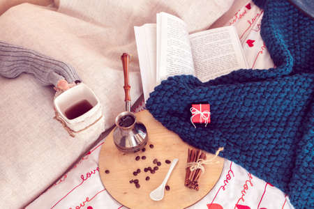 Cozy still life of breakfast in bed for St.Valentine's Day. Coffee with small gift and plaid with book on a background