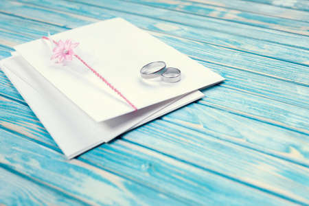 Envelope decorated with pink flower and two wedding rings on blue background