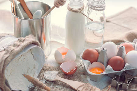 ingredient for baking as an eggs, flour, milk and water on a table