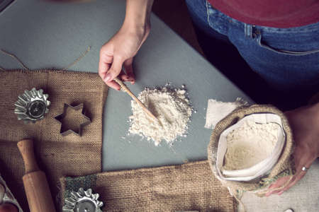 Female hands pick flour with a spoon  for preparation of cookies 版權商用圖片