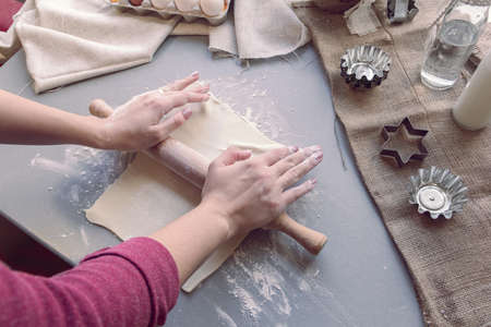 Preparation for baking cookies: female hands roll out the dough
