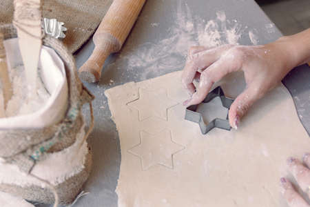 woman's hands cutting the dough with a baking tin in a star shape