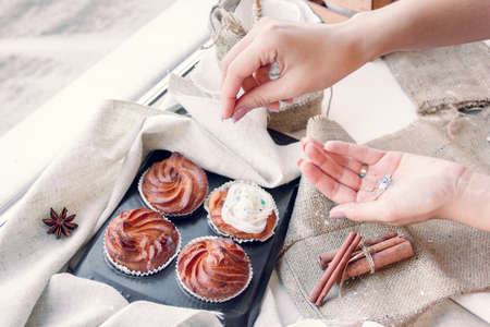 Women's hands decorate cupcakes