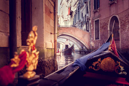 The gondolier floats on a narrow canal in Venice under the bridge, view from gandola