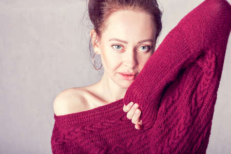 portrait of a girl in a burgundy knitted sweater with bare shoulder