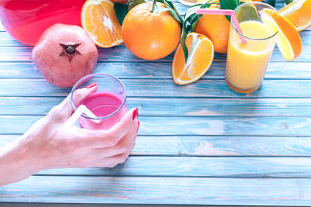 freshly squeezed pomegranate juice in a women's hand with oranges and pomegranate fruit on a blue wooden background