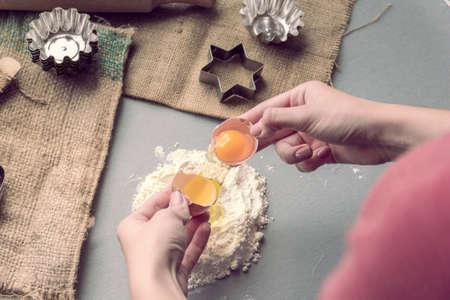 Female hands break a chicken egg into flour Foto de archivo