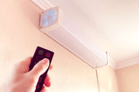 hand from remote-controlled includes bactericidal air recirculator hanging on wall for quartzing air in room 版權商用圖片 - 144491857