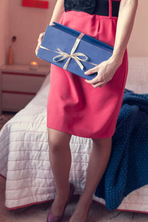 girl in a red dress hold a gift in her hands, standing near the bed Stok Fotoğraf