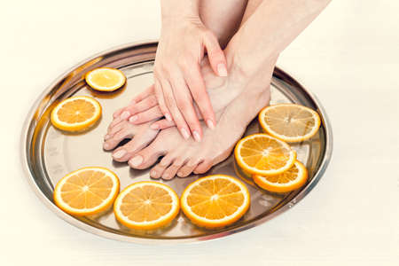 pedicure and manicure in the spa salon with sliced orange on a white wooden background Stok Fotoğraf