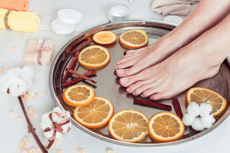 pedicure in the spa salon with sliced oranges, cinnamon and cotton on a white wooden background 版權商用圖片 - 143717530