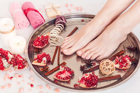 pedicure in the spa salon with pomegranate, cinnamon and anise on a white wooden background
