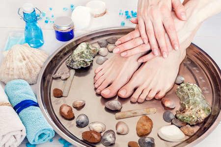 pedicure and manicure in the spa salon with seashells and stones on a white wooden background Stok Fotoğraf